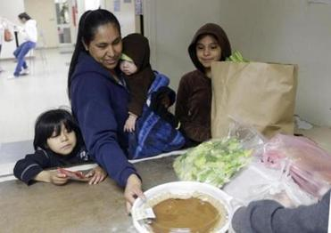 A family receives aid at the community center food pantry. Wages are stagnant for Silicon Valley's low-skilled workers.